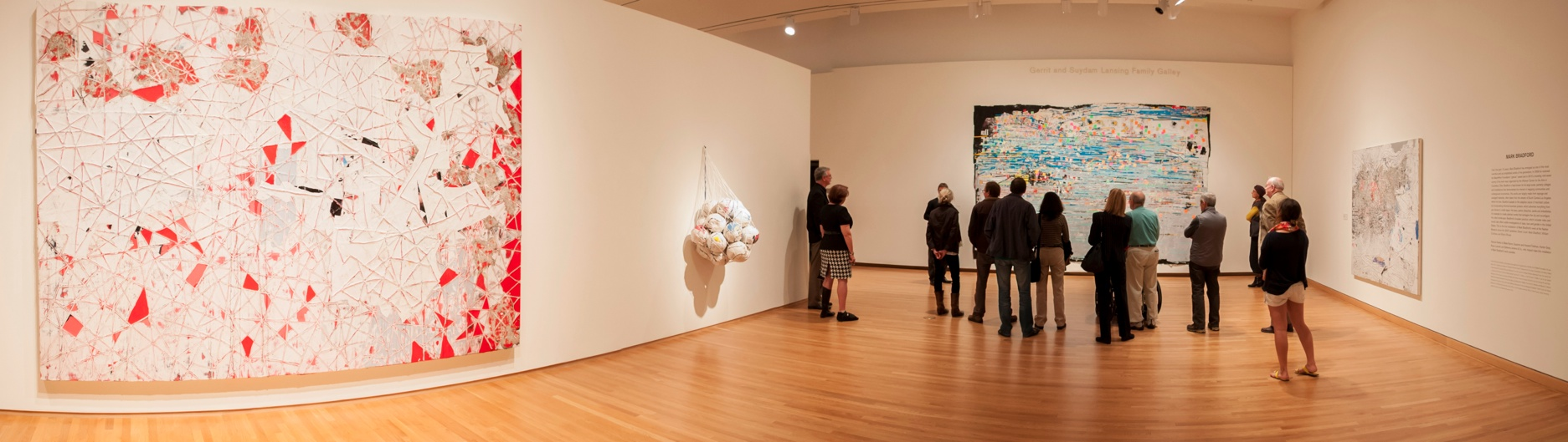 Visitors tour an installation of Mark Bradford's work, including his mixed media work Red Painting, Soccer Ball Bag 4 and Potable Water with Trevor Schoonmaker, Chief Curator and Patsy R. and Raymond D. Nasher Curator of Contemporary Art.
